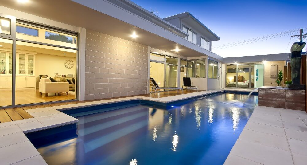 Pool landscaping guide Clean landscaping around the pool with large tiles and timber decking