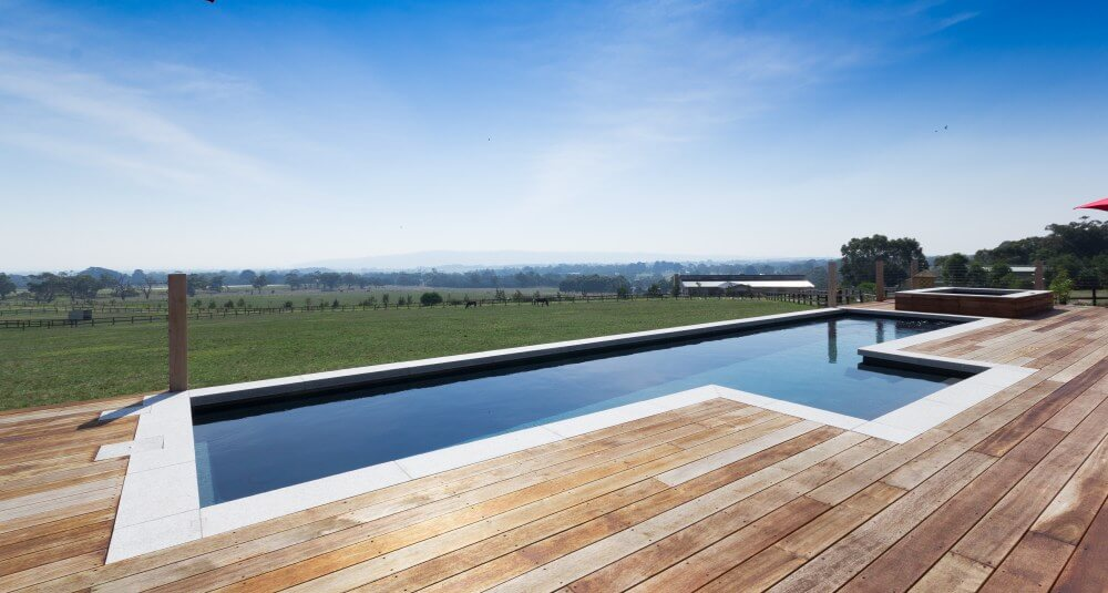 Simplistic pool landscaping with coping and timber decking