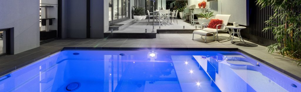 Compass fibreglass plunge pool at night with light on
