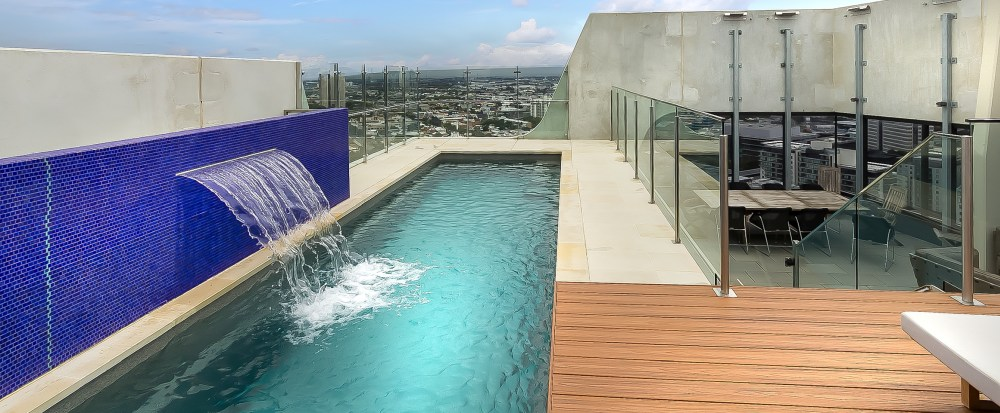 Fastlane lap pool with water wall feature installed above the ground